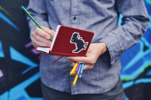 AW_writing challenge torso of a man as he holds a red notebook